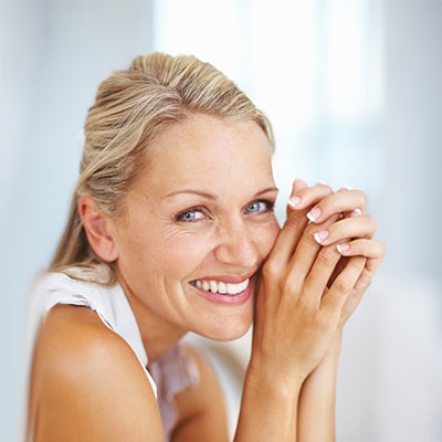 A mature woman smiling because of the cosmetic dental services available from this dentist in Golden, CO