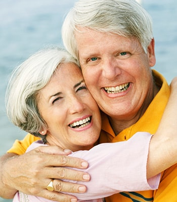 An older couple smiling after enjoying restorative dentistry from Genesee Dental Group