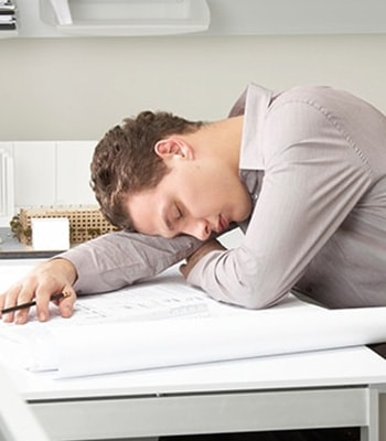 A young man sleeping on his desk, suffering from Sleep Apnea