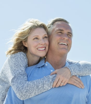 Couple smiling with beautiful dental implants